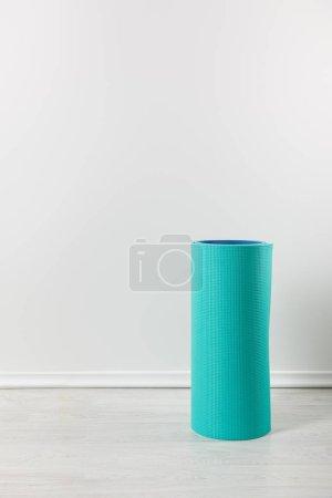 Photo pour Un tapis de fitness bleu sur le sol à la maison - image libre de droit
