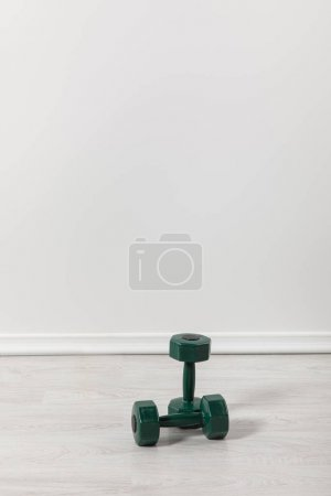 Photo for Two green dumbbells for fitness on floor - Royalty Free Image