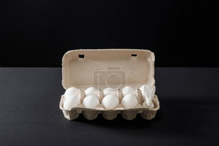 Photo pour Egg tray with chicken eggs and decorative bunny on grey and black background - image libre de droit