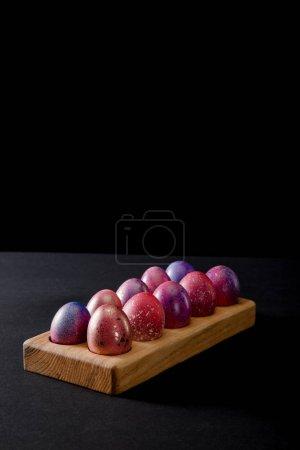 Photo pour Œufs de Pâques colorés sur planche de bois sur fond gris et noir - image libre de droit
