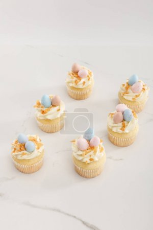 Photo pour Délicieux cupcakes de Pâques avec des œufs de caille peints sur le dessus sur fond blanc - image libre de droit