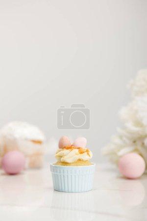 Photo pour Concentration sélective du cupcake avec des œufs de Pâques sur fond gris - image libre de droit