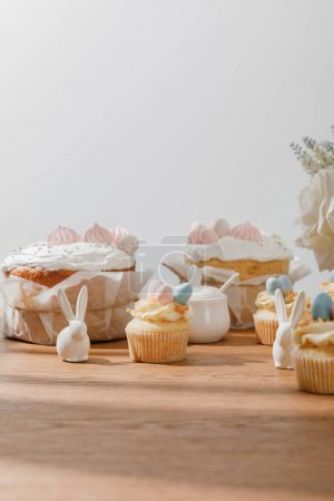 Photo for Selective focus of cupcakes with decorative bunnies, sugar bowl, easter cakes and flowers isolated on grey - Royalty Free Image