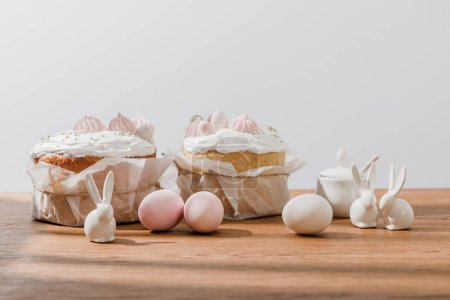 Photo for Decorative bunnies, chicken eggs, sugar bowl and Easter bread isolated on grey - Royalty Free Image