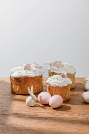 Photo for Decorative bunny, chicken eggs, sugar bowl with Easter cakes isolated on grey - Royalty Free Image