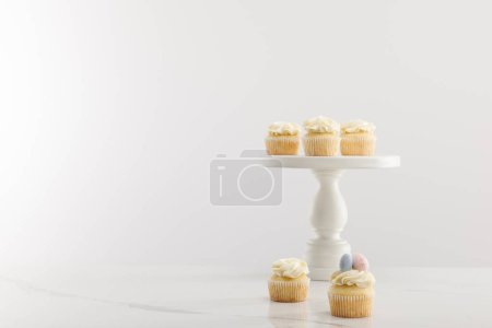 Photo for Tasty easter cupcakes on cake stand isolated on grey - Royalty Free Image