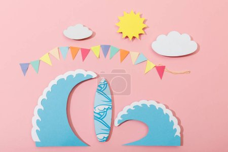 Photo pour Top view of paper cut sun, clouds, flags, surfboard and sea waves on pink background - image libre de droit