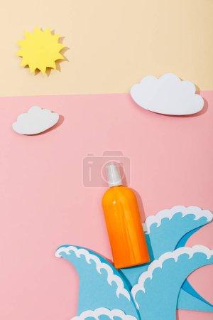Vista superior de papel cortado olas de mar, nubes, sol y botella de protector solar en rosa y beige