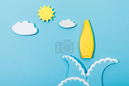 Top view of paper cut sea waves, clouds and sun with tube of sunscreen on blue