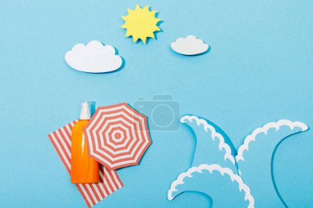 Photo for Top view of paper cut beach with waves and bottle of sunscreen on blue background - Royalty Free Image