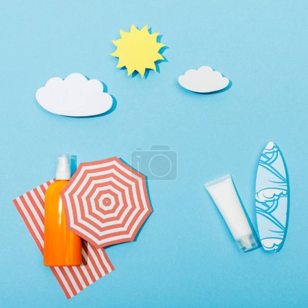 Photo for Top view of paper cut beach with bottle and tube of sunscreen on blue background - Royalty Free Image