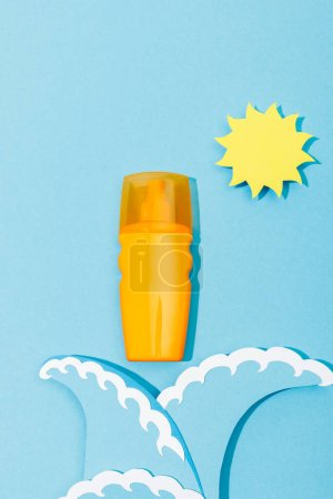 Photo for Top view of paper cut sun and sea waves with dispenser bottle of sunscreen on blue background - Royalty Free Image