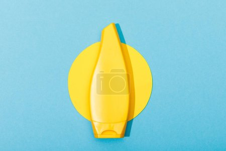 Photo for Top view of tube of sunscreen on paper cut sun on blue background - Royalty Free Image