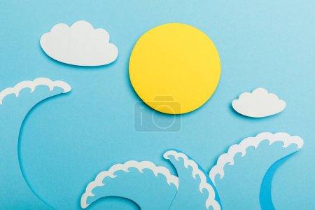 Draufsicht auf Papier geschnittene Sonne, Wolken und Meereswellen auf Blau