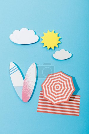 Photo for Top view of paper cut beach with surfboards, umbrella and blanket on blue background - Royalty Free Image