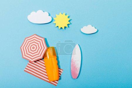 Photo pour Vue de dessus de la plage de papier découpé avec planches de surf, parapluie, couverture et bouteille de crème solaire sur bleu - image libre de droit