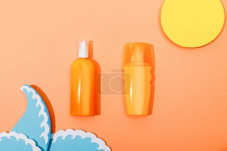 Photo pour Vue du dessus des bouteilles de distributeur de crème solaire avec du papier coupé soleil et vagues de mer sur fond orange - image libre de droit