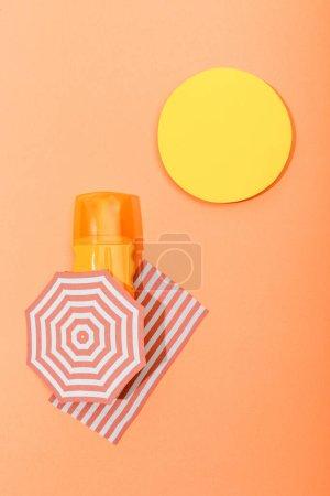 Photo pour Haut vue de papier coupé soleil, parasol et couverture avec distributeur bouteille d'écran solaire sur orange - image libre de droit
