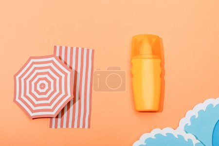 Photo for Top view of dispenser bottle of sunscreen with paper cut sea waves on orange background - Royalty Free Image