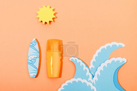 Top view of dispenser bottle of sunscreen with paper cut sea waves, sun and surfboard on orange