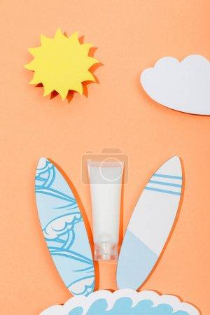 Foto de Vista superior del papel cortado sol, nube, olas marinas y tablas de surf con tubo de protector solar en naranja. - Imagen libre de derechos