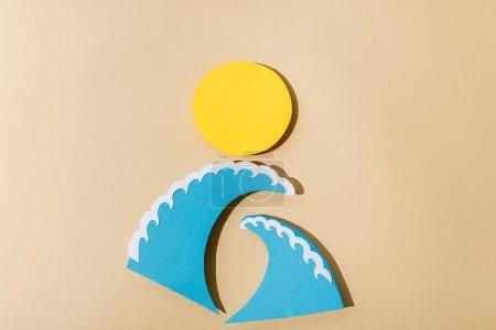 Photo pour Vue du dessus du papier coupé soleil et vagues de mer sur fond beige - image libre de droit