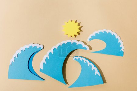 Photo for Top view of paper cut sun and sea waves on beige - Royalty Free Image