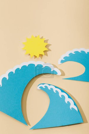 Photo pour Vue du dessus du papier coupé soleil et vagues de mer bleues sur beige - image libre de droit