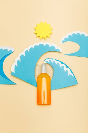 Photo for Top view of paper cut sun and sea waves with dispenser bottle of sunscreen on beige - Royalty Free Image