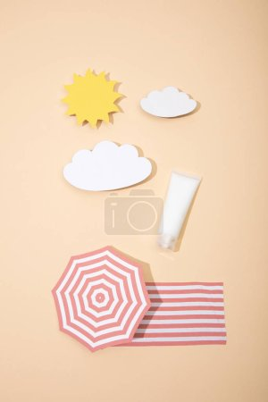 Photo for Top view of paper cut sun, clouds, beach umbrella and blanket with tube of sunscreen on beige - Royalty Free Image