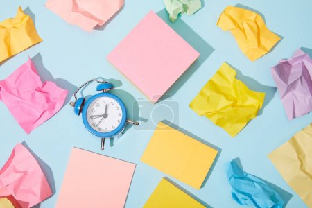 Photo for Top view of classic alarm clock with colorful sticky notes on blue background - Royalty Free Image