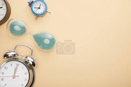 Photo pour Top vue des réveils classiques et du sablier sur fond beige - image libre de droit