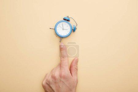 Photo pour Crochet vue d'un homme touchant un petit réveil sur fond beige - image libre de droit