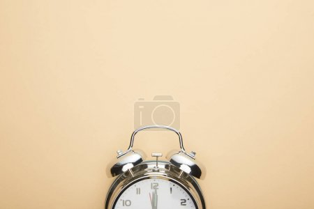 Photo for Top view of classic alarm clock on beige background - Royalty Free Image