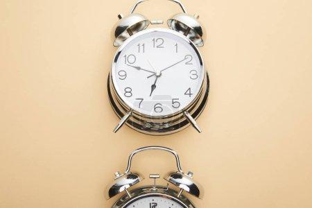 Photo pour Top vue du réveil classique sur fond beige - image libre de droit