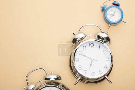 Foto de Vista superior de los relojes de alarma clásicos sobre fondo beige. - Imagen libre de derechos