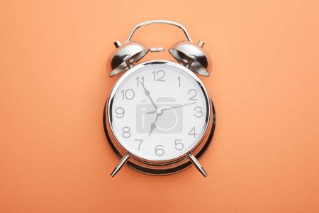 Photo for Top view of classic alarm clock on peach background - Royalty Free Image