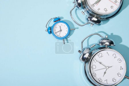 Photo for Top view of classic alarm clocks on blue background - Royalty Free Image