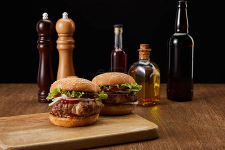 Two burgers on wooden chopping board, oil, beer and vinegar bottles, pepper and salt mills isolated on black