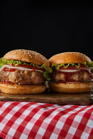Photo for Two hamburgers on wooden chopping board on checkered tablecloth isolated on black - Royalty Free Image