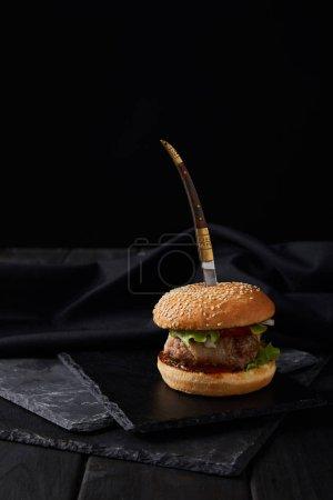 knife pierced in hamburger on dark cutting boards isolated on black