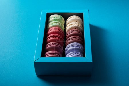Photo for Assorted delicious colorful french macaroons in box on blue background - Royalty Free Image