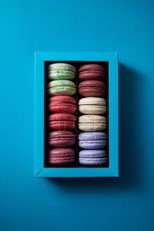 Photo for Top view of assorted delicious colorful french macaroons in box on blue background - Royalty Free Image