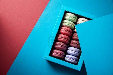 Photo pour Vue du dessus de macarons français colorés mordus délicieux assortis en boîte sur fond bleu et rouge - image libre de droit