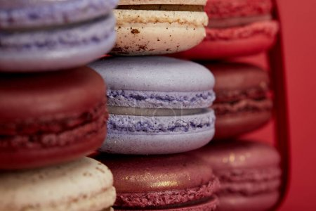 stack of assorted delicious colorful french macaroons on red background