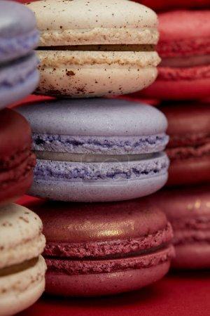 Photo pour Un assortiment de macarons français colorés sur fond rouge - image libre de droit