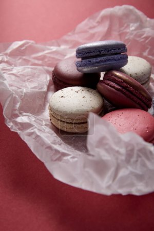 close up view of assorted delicious colorful french macaroons on crumpled paper on red background