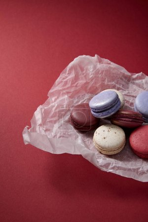 assorted delicious colorful french macaroons on crumpled paper on red background