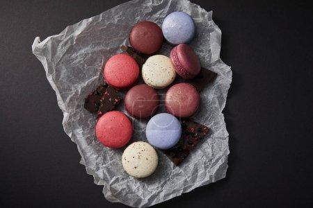 Photo pour Vue de dessus de macarons français colorés assortis délicieux sur papier froissé avec du chocolat sur fond noir - image libre de droit