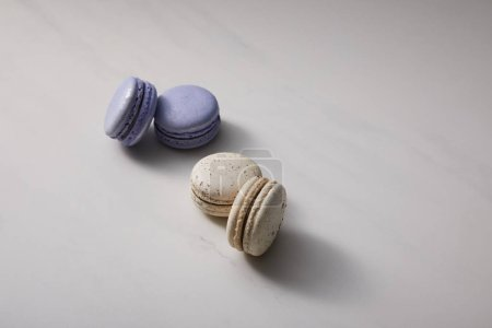 Photo for Assorted delicious violet and white  french macaroons on grey background - Royalty Free Image